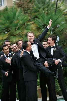 Men in tuxedos pick up the groom outside