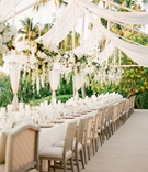 Wedding reception with a long table under suspended floral arrangements and chandeliers