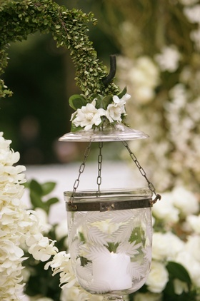 Etched glass vessel holding a candle decorates a wedding aisle