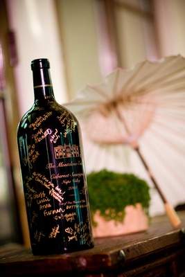 Black wine bottle guest book with gold signatures