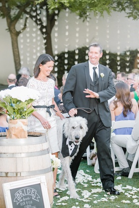 Mother of the bride in a lace Byron Lars dress escorts dog with father of the bride in black tuxedo