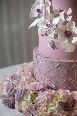 Wedding cake with white sugar flower with purple center fresh flower base silver web design sequins