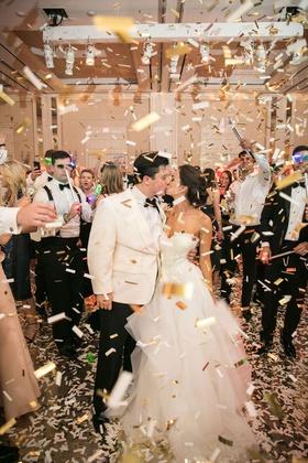 bride in strapless ball gown wedding dress groom white tuxedo white gold confetti end of night kiss