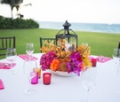 Outdoor puja engagement dinner table with yellow and fuchsia orchids, red and orange roses, lantern