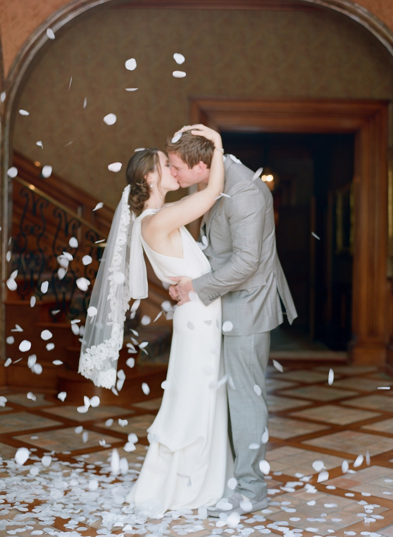 Bride and groom kissing with white flower petals around them