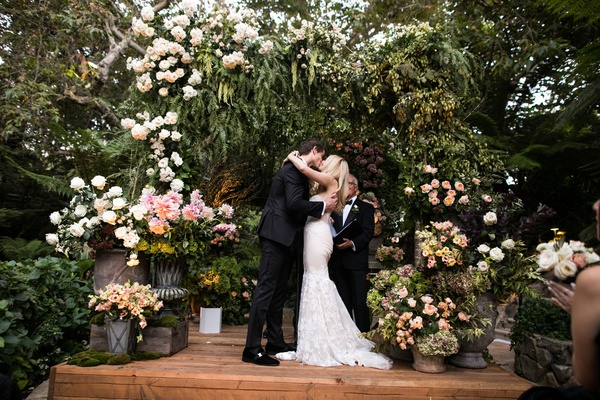 wedding ceremony wood stage greenery white blush flowers chuppah first kiss jewish ceremony fall