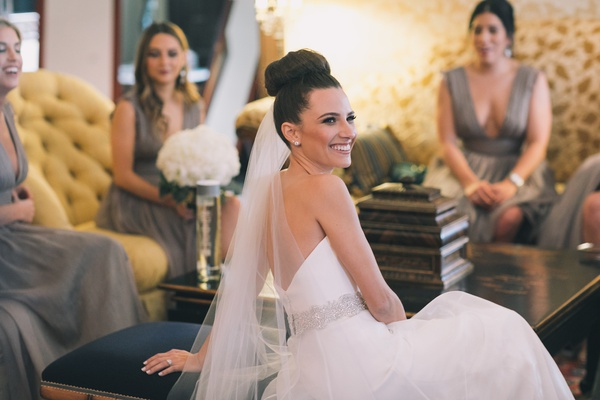 bride in romona keveza, beaded belt, sock bun, lounging with bridesmaids