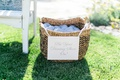 Light blue flip flops in wicker basket with sign attached in ribbon for dancing at wedding