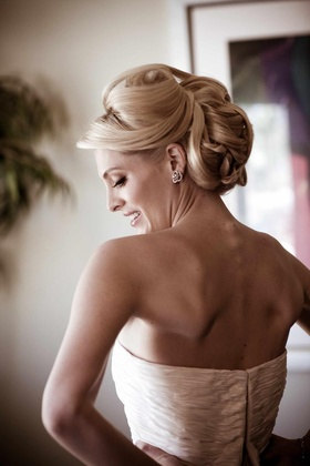 Bride getting dress zipped with hair and makeup done