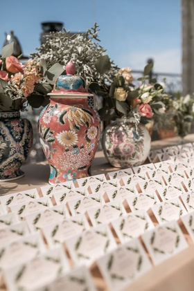 wedding reception escort card table boho chic vintage style painted jars and flowers