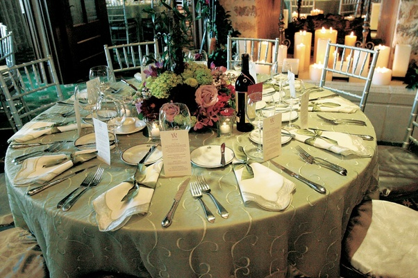 Wedding reception table with green tablecloth and red, green, and lavender flowers