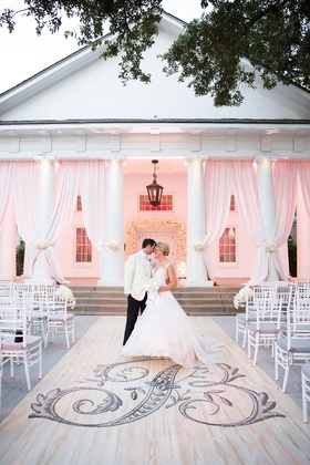 Wedding portrait in front of ceremony decor large monogram on aisle runner pink drapes white chairs