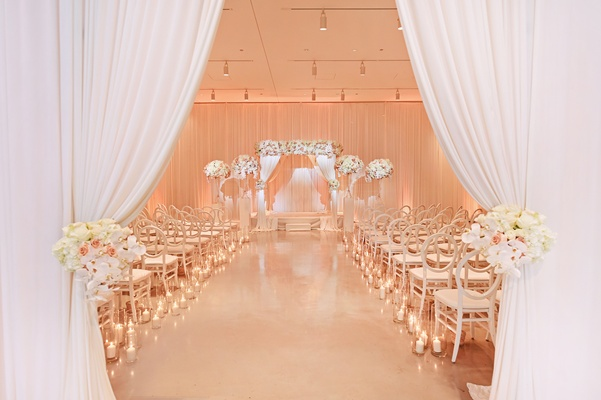 entrance to ceremony with white curtains held back by blush and ivory flower arrangements