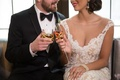 Bride and groom toast with gold swirl tumbler and champagne flute