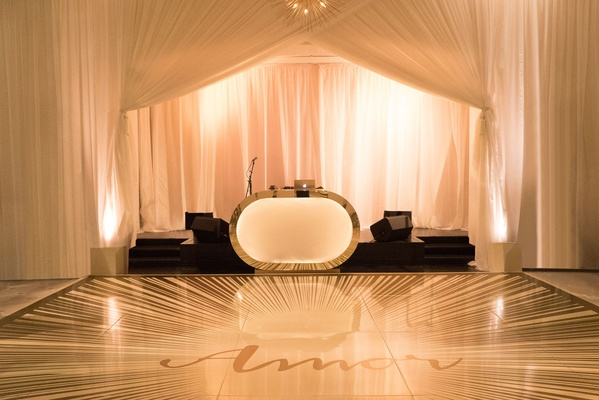 DJ booth with silver gold metallic border and custom dance floor wedding amor with sunburst motif