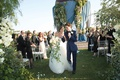 bride in vera wang ball gown with cascading bouquet and groom in navy tuxedo during recessional