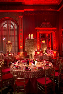 Gold beaded chandelier centerpiece and red lighting