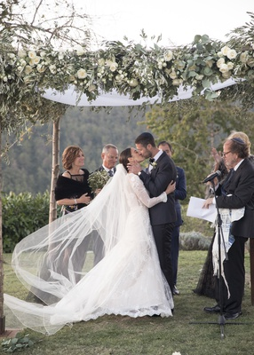 bride and groom kiss under chuppah with natural posts, ivory flowers, and greenery