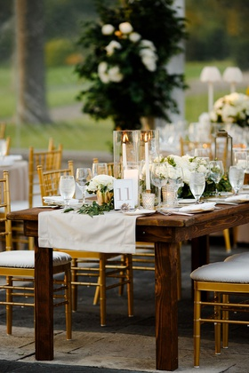 wedding reception clear tent dark wood table gold chairs linen runner garland taper candles