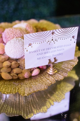 Shell nuts and decorated eggs on gold plate sofreh table
