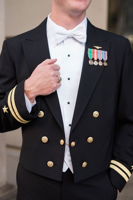 Groom in navy uniform with bow tie and decorations on lapel