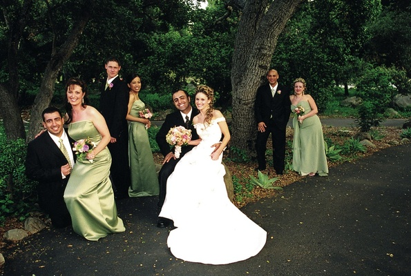 Bride and groom with green bridesmaids in woods