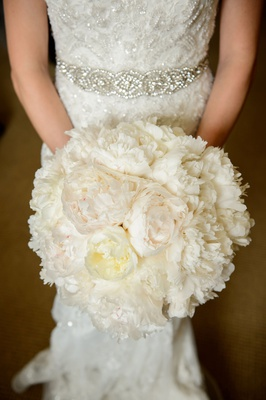 Bride in beaded wedding dress crystal belt sash holding white ivory bouquet of peony flowers