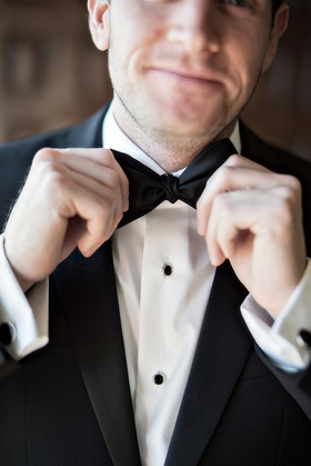 groom fixing his bowtie black white tuxedo smirk wedding