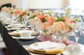 Bridal shower table with floral runner of pink, white and orange flowers in round vases with glitter
