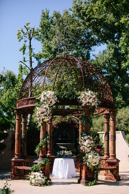 rusted rustic dome ceremony altar with floral arrangement on columns