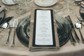 Black and white menu with gold print on gold napkin