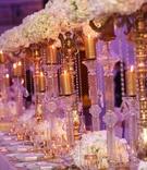 Wedding reception table with golden candelabra, candles, and gold-rimmed glassware and chargers