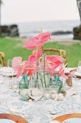 Sea glass vases filled with pink anthuriums