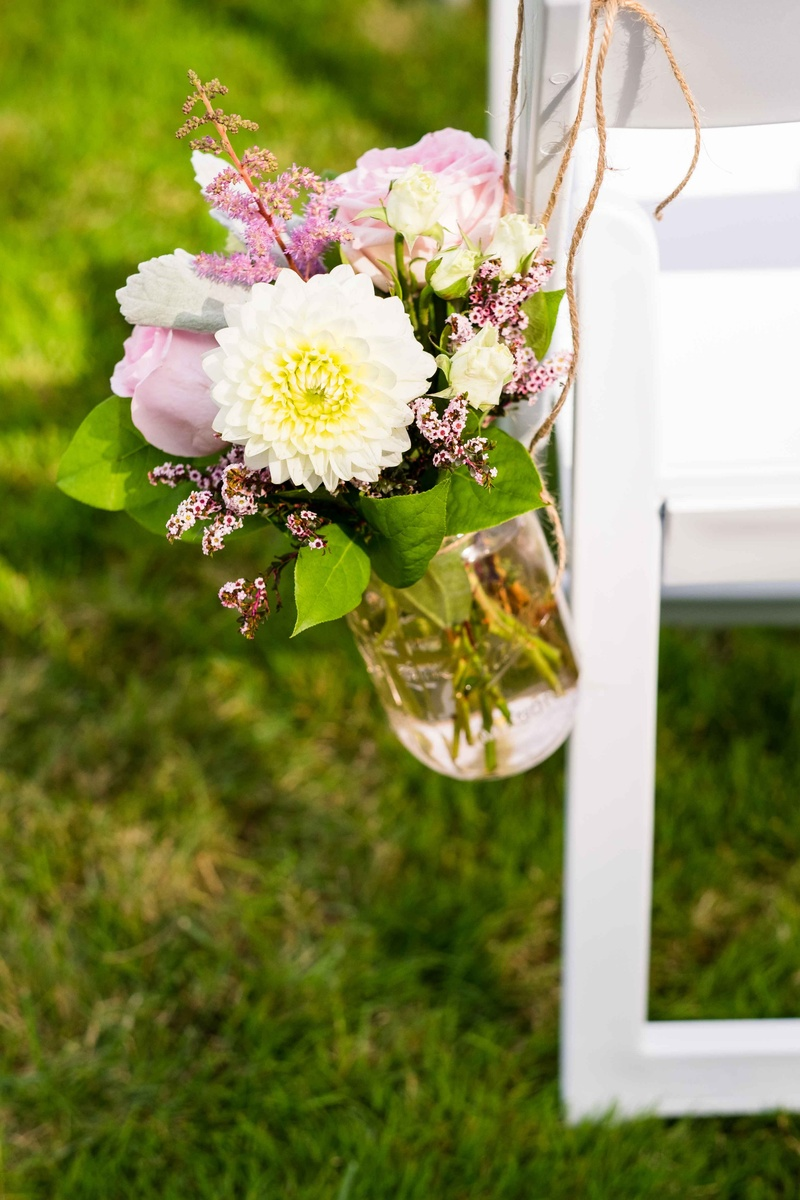 Ceremony dcor photos small floral arrangement hanging on chair a small floral arrangement of white and pink flowers and foliage glass vase hanging white chair reviewsmspy
