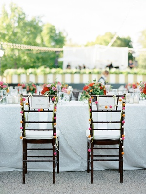 Bride and groom wedding chairs with pom pom garland decorations