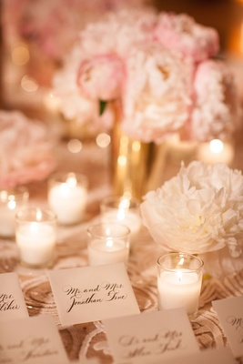 Texture linens with pink peony and white peony flowers candle votives gold vases escort card table