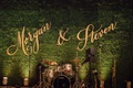 Wedding reception calligraphy cutout signs on green hedge wall behind live band stage
