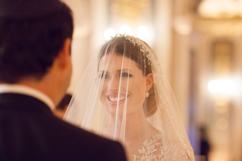 Bride looking into groom's eyes during wedding ceremony long sleeve dress with illusion details veil