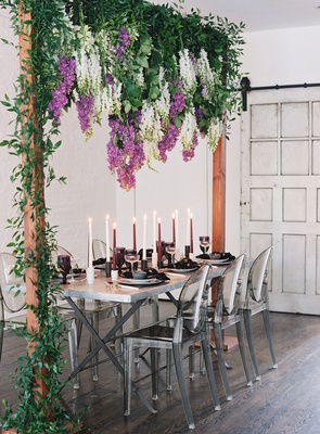 wedding table silver ghost chairs tall candles wisteria purple white greenery wood arch industrial