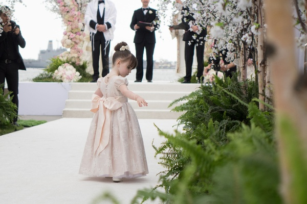 Flower girl walking down white aisle toward altar throwing flower petals bow in back of dress