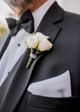 boutonniere with three white roses wrapped with pearl beading and gold detailed black ribbon