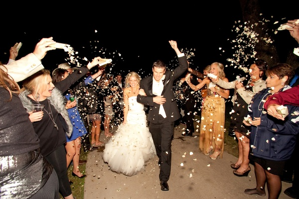 Bride and groom walk through tunnel of guests with heart confetti