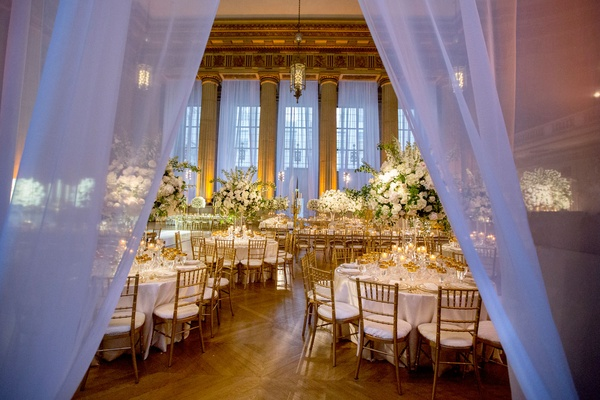 Wedding reception drapery at entrance tall ceilings windows white tables gold chairs tall flowers