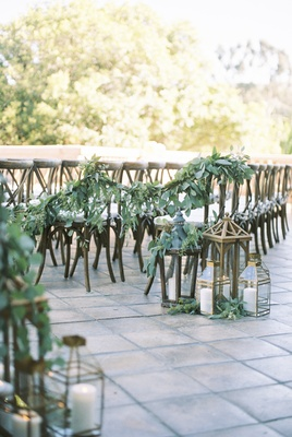 eucalyptus garland connect rows of chairs at ceremony, lanterns at aisle