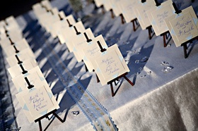Wedding guest place cards are set on miniature easels