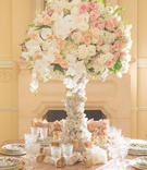 Wedding reception table with white, pink, peach roses, orchids, asiatic lilies on quartz stand