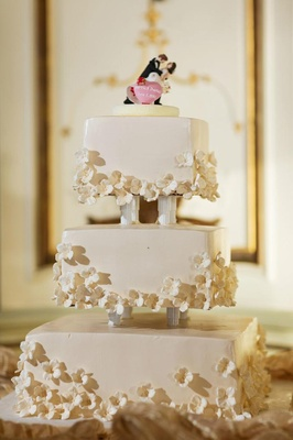 White wedding cake with square tiers and small white sugar flowers