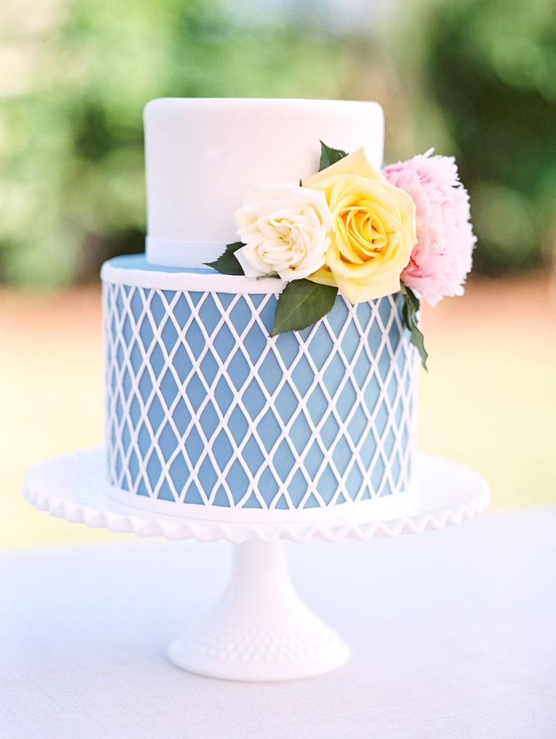 Wedding cake just for cutting blue and white diamond design on bottom fresh flowers on top fondant