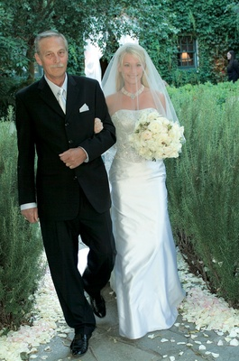 Father of bride walks bride, wearing a strapless gown with a beaded bodice, down the aisle