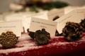 Winter wedding with escort cards in pinecones on table with red tablecloth, fake snow